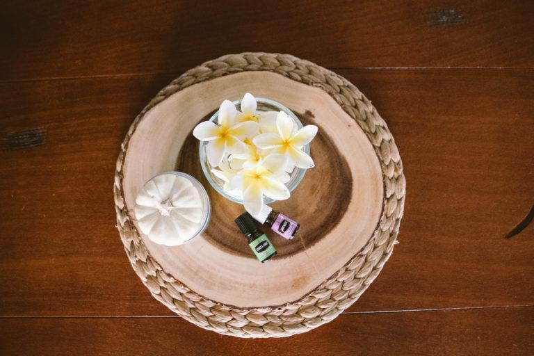 Essential oils with pumpkin and plumerias on stump